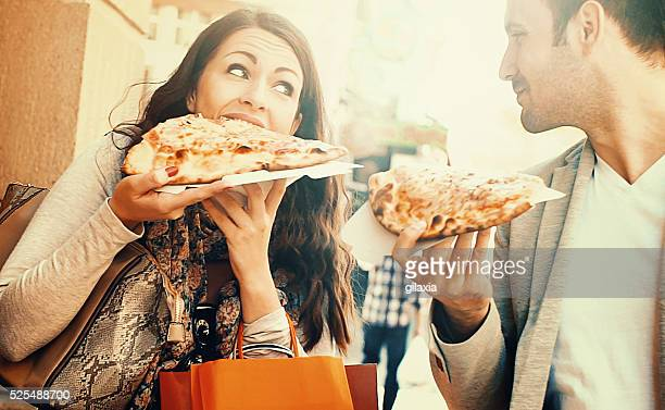 Couple eating pizza while walking.