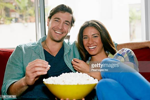 Couple eating popcorn on sofa