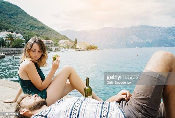 Couple eating sandwiches and drink wine at Kotor bay