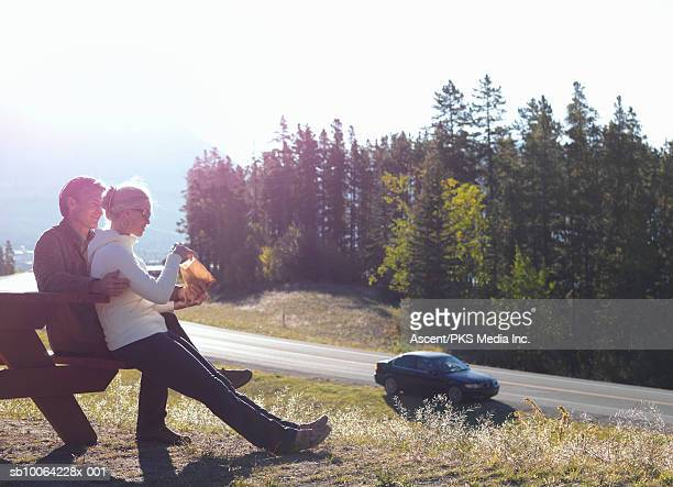 Couple eating snack on bench, car parked on road in background