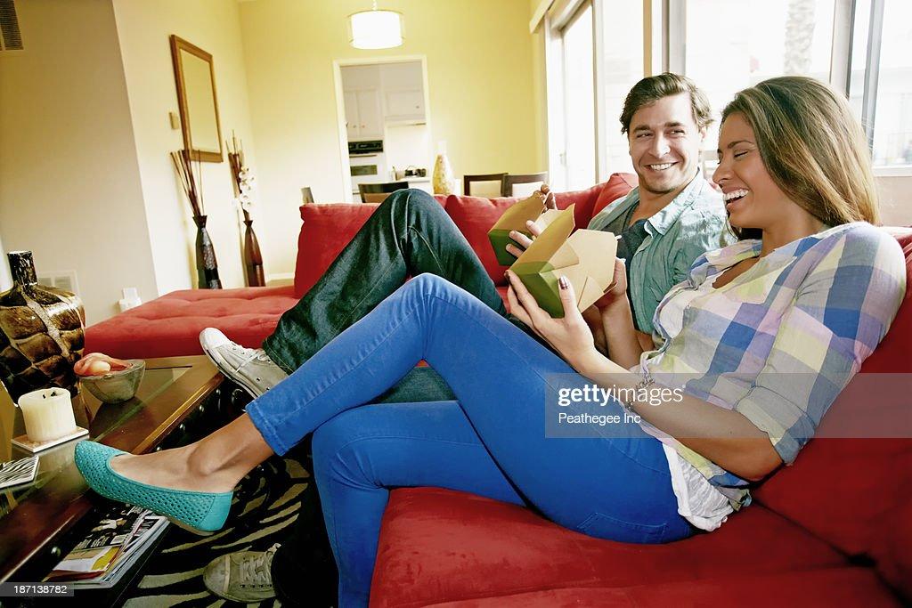 Couple eating take out food on sofa