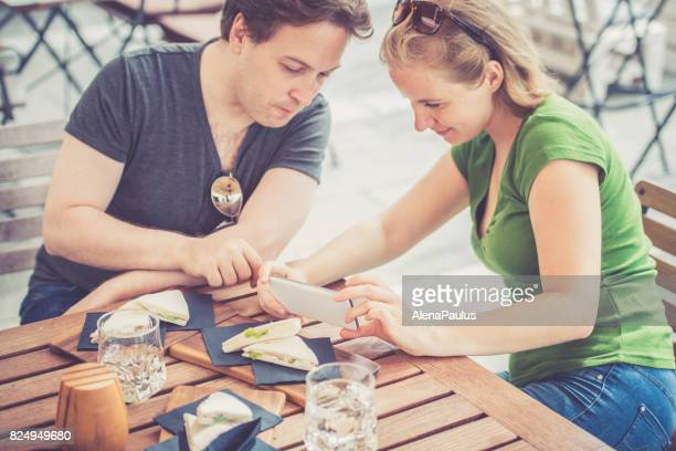 Couple eating tramezzini - italian sandwiches and taking food photos outdoors