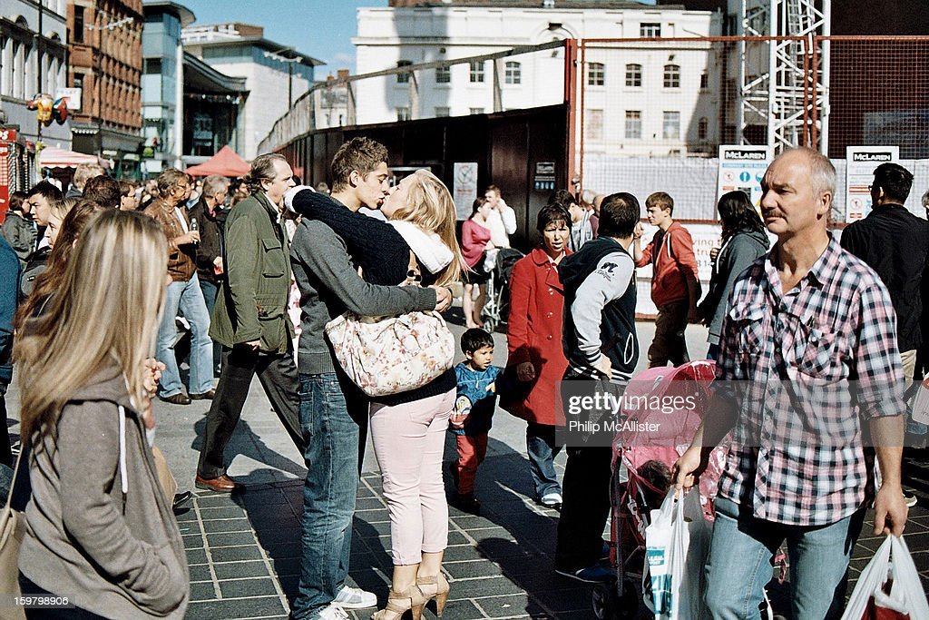 CONTENT] Couple embrace and kiss in a public space. Two young lovers show affection on a public street.