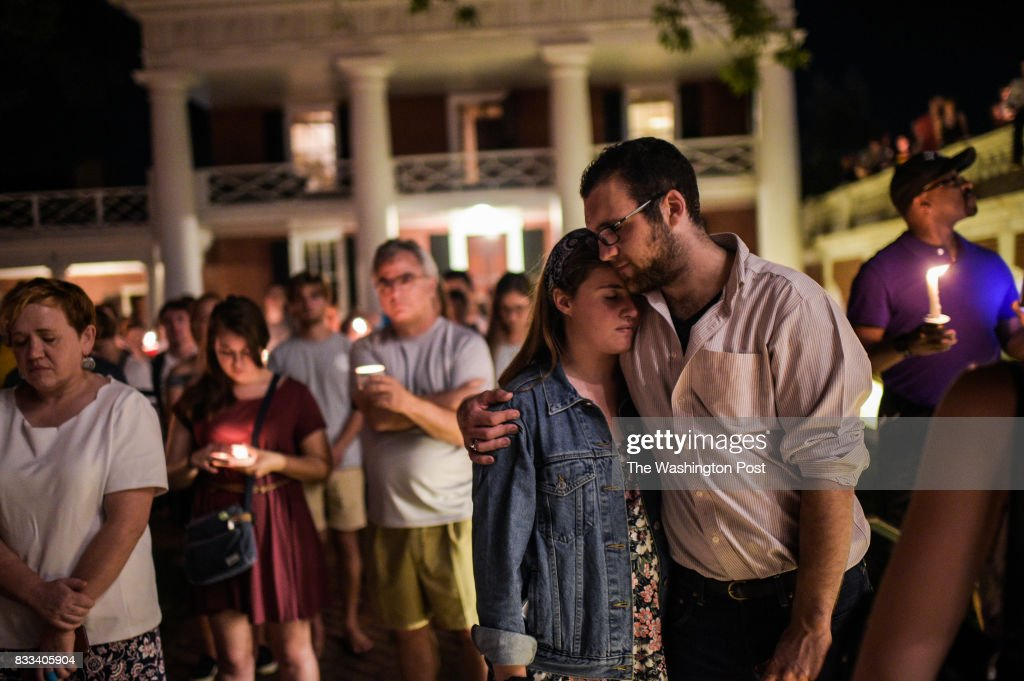 A couple embrace as they join hundreds of people marching peacefully with lit candles across the University of Virginia campus on Wednesday, August 116, 2017, in Charlottesville, VA, in the wake of violence in the city and against torch-lit white nationalist parade the same campus last Friday night.