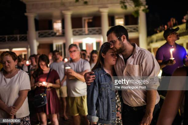 A couple embrace as they join hundreds of people marching peacefully with lit candles across the University of Virginia campus on Wednesday August...