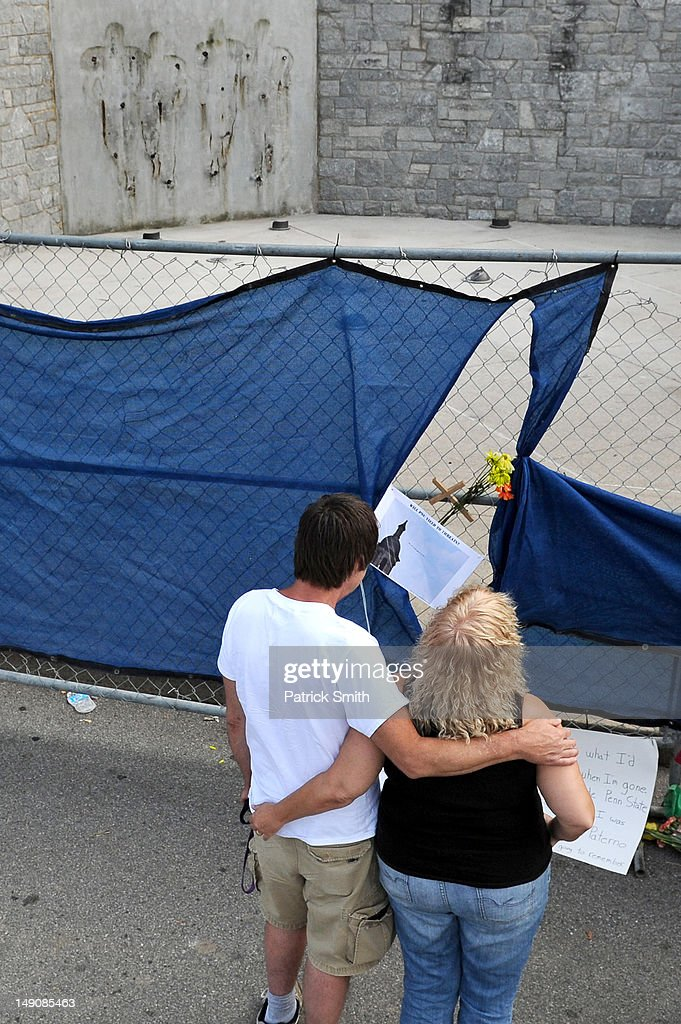 A couple embrace at the site where the statue of former Penn State University football coach Joe Paterno once stood outside Beaver Stadium on July 22, 2012 in State College, The statue was removed by workers after Pennsylvania. Penn State's president Rodney Erickson made the decision Sunday in the wake of the child sex scandal of former assistant football coach Jerry Sandusky. According to an FBI report, it is believed that Paterno had detailed knowledge of Jerry Sandusky sexually abusing children before and after Sandusky retired from coaching at Penn State.