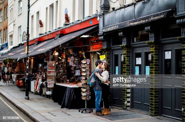 A couple embrace near shops at at Portobello Road Market in the Notting Hill district of west London on August 8 2017 Last week The Bank of England...