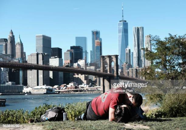 A couple embrace on the grass along a promenade in Brooklyn on an unseasonably warm day on October 20 2017 in New York City Temperatures across New...