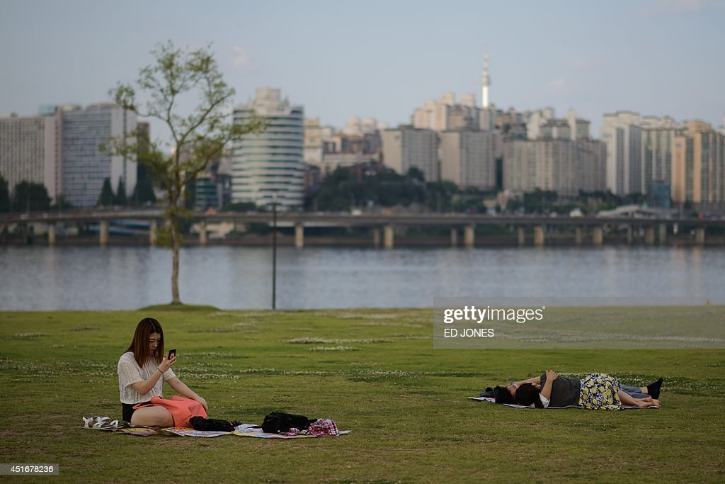 A couple embraces as a woman uses a smartphone in a park in Seoul on July 4, 2014. Despite a widely reported increase in tolerance towards public displays of affection, moderate intimacy between young couples in Seoul is largely limited to the city's quieter areas. Many aspects of South Korean culture maintain Confucian roots which value community over individuals and frown upon individualistic behaviour. AFP PHOTO / Ed Jones