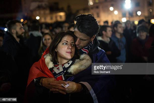 A couple embraces as people hold a vigil for victims of the Paris terrorist attacks in Trafalgar Square on November 14 2015 in London England Several...
