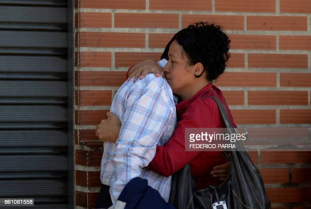 A couple embraces before boarding a bus at a station in Caracas on October 11 2017 as scores of disappointed Venezuelans who see no end to the crisis...