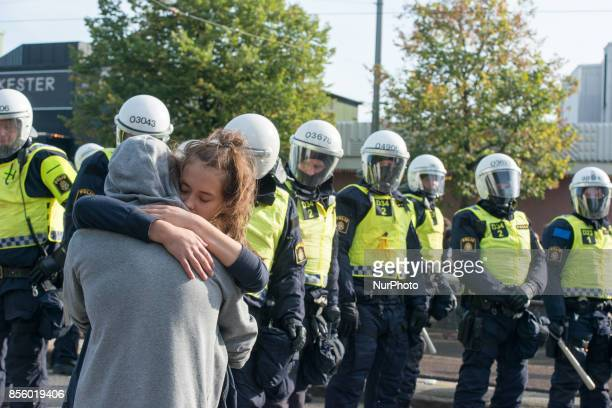 A couple embraces in front of a row of riot police during an antifascist protest to denounce a march by the Nordic Resistance Front through central...