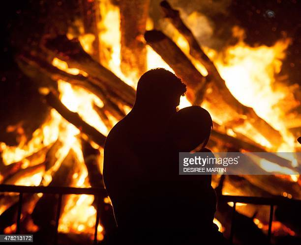 A couple embraces next to the flames of a bonfire during the traditional Saint John night which coincides with the summer solstice at the beach of...