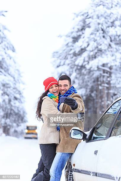 Couple embracing and making selfie on snow path