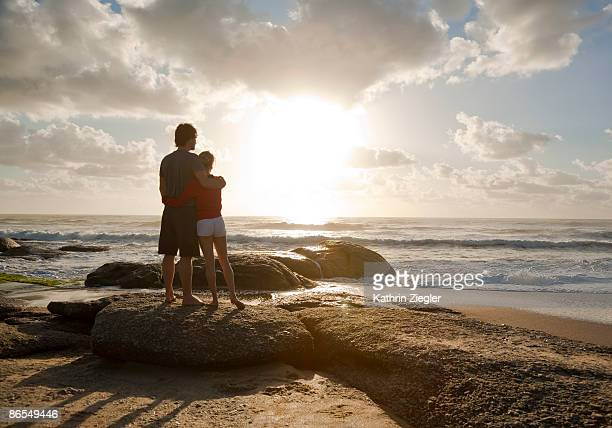 Couple embracing at the beach, sunrise