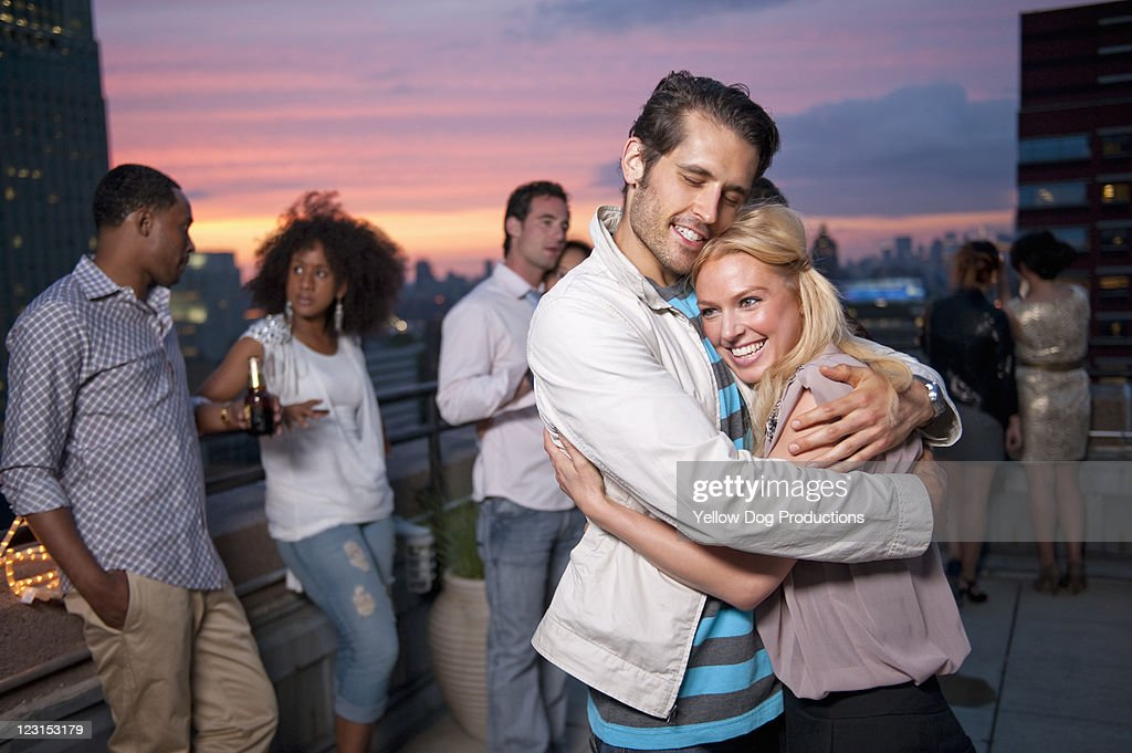 Couple Embracing at Urban Rooftop Party : Stock Photo
