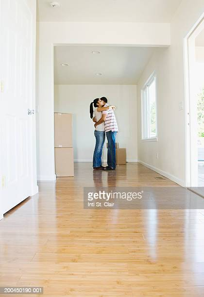 Couple embracing beside stacks of cardboard boxes in living room