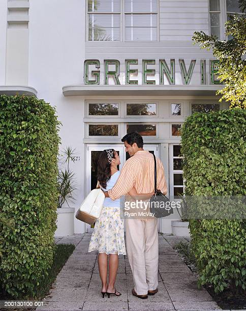 Couple embracing by hotel entrance, rear view