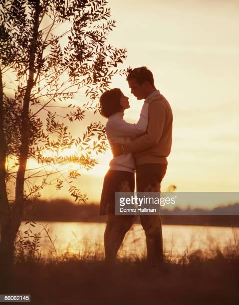 Couple embracing by lake at dusk