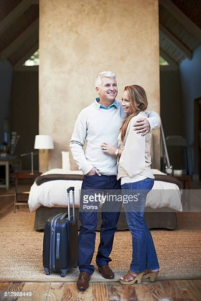 Couple embracing by luggage in hotel bedroom