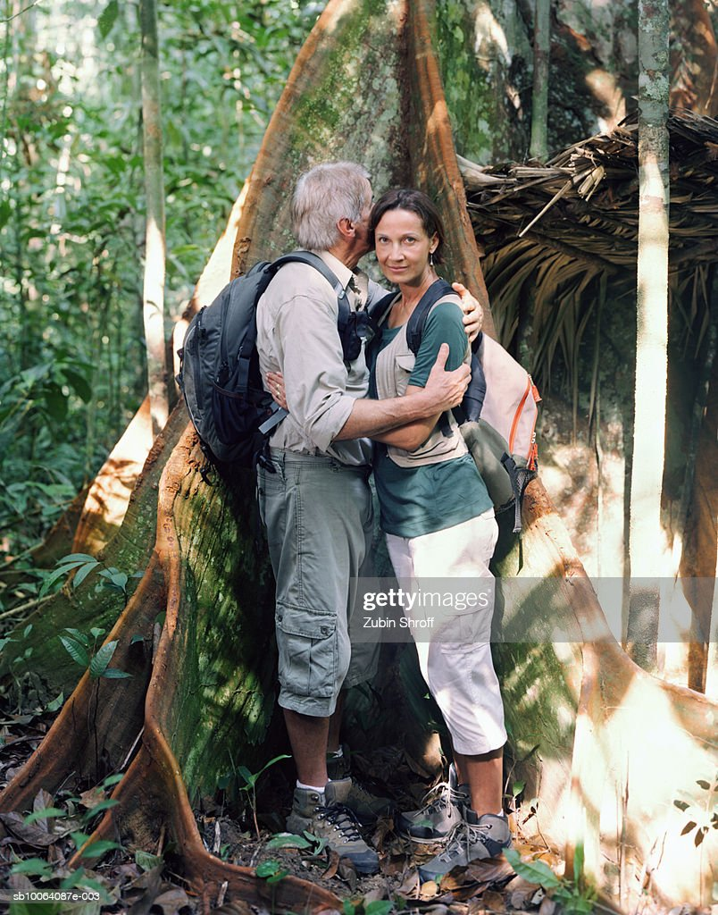 Couple embracing by tree trunk in rainforest, side view : Stock Photo