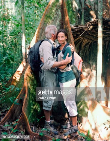 Couple embracing by tree trunk in rainforest, side view : Foto de stock