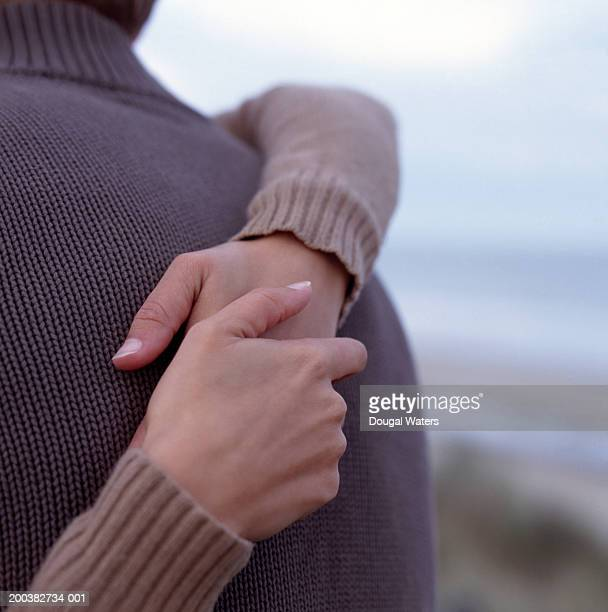 Couple embracing, close-up of hands