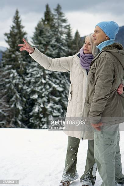 Couple embracing each other in snow, woman pointing on something