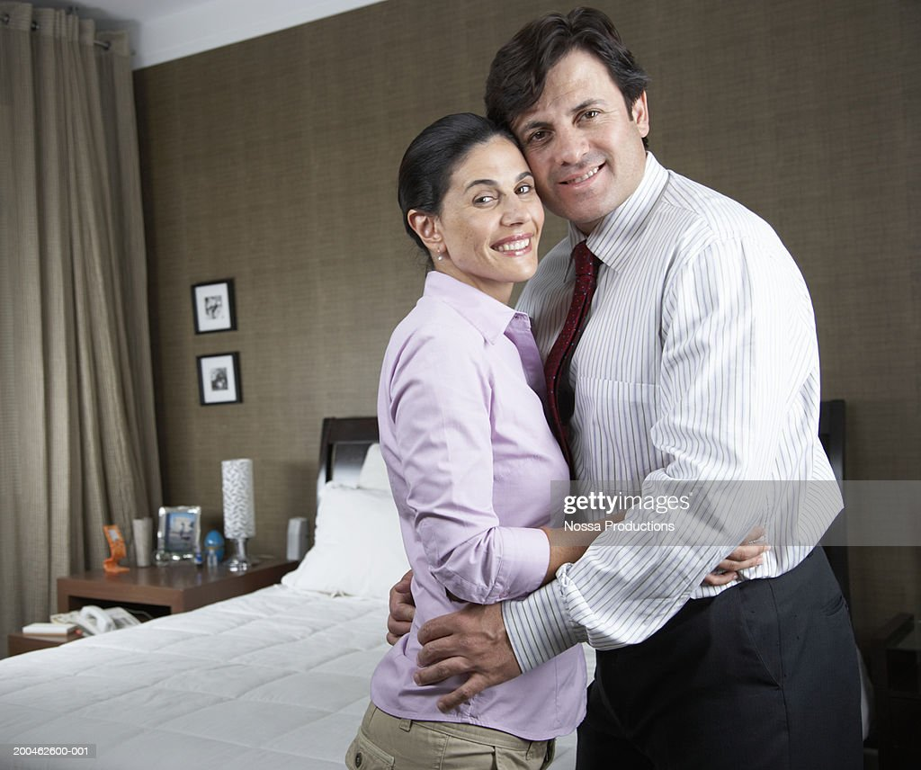 Couple embracing in bedroom, portrait : Stock Photo