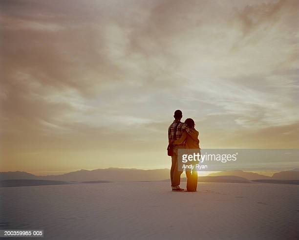 Couple embracing in desert, watching sunset, rear view