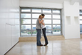 Couple embracing in empty apartment
