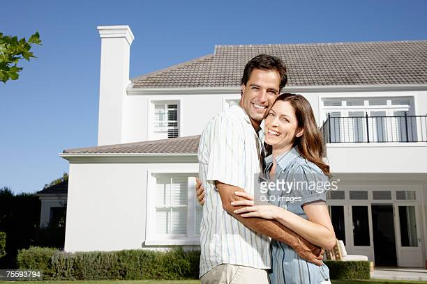 Un couple embrassant face à une grande maison