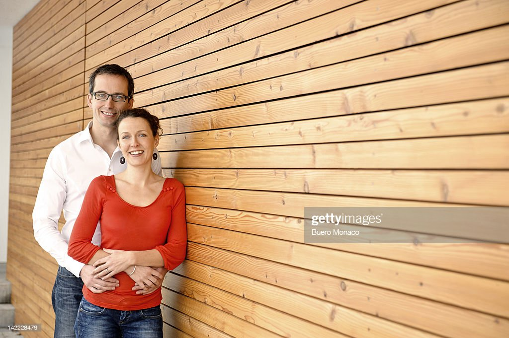 Couple embracing in front of new home, smiling : Stock Photo