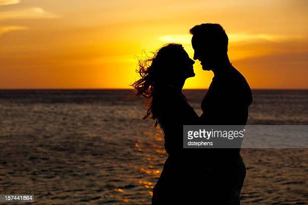 Couple embracing in front of romantic sunset