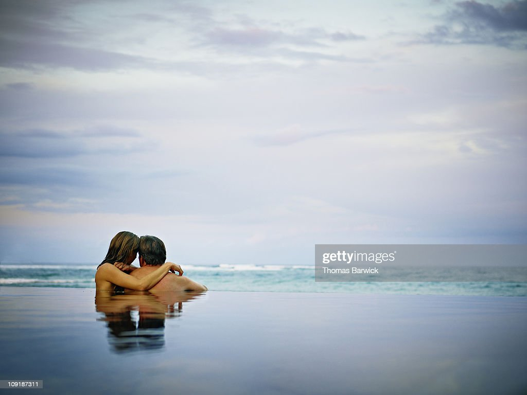 Couple embracing in infinity pool rear view : Stock Photo