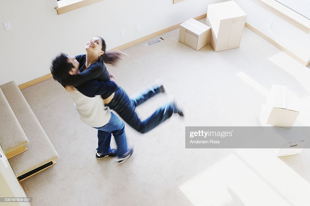 Couple embracing in living room, elevated view (blurred motion) : Stock Photo