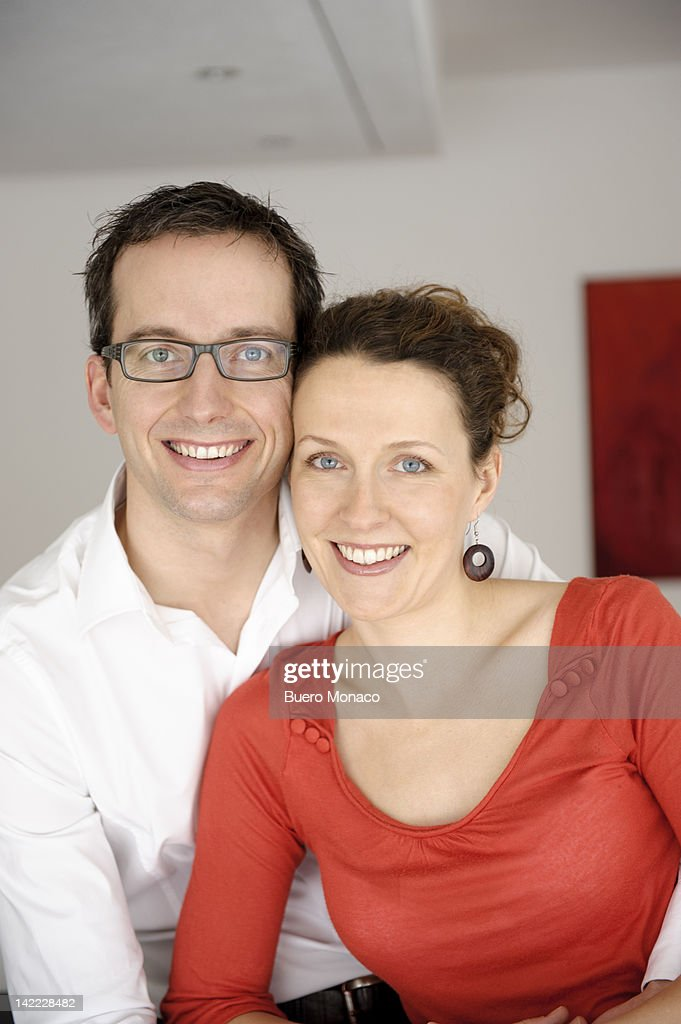Couple embracing in new home, smiling : Stock Photo