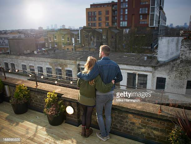 Couple embracing in roof garden, looking over city