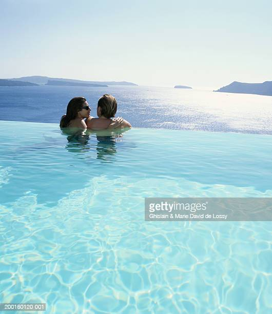 Couple embracing in swimming pool by ocean, rear view