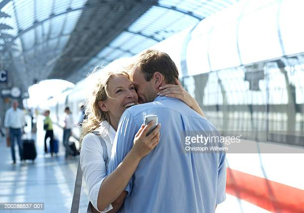 Couple embracing in train station, woman holding mobile phone