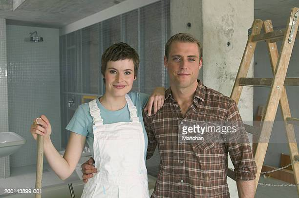 Couple embracing in unfinished house, smiling, portrait