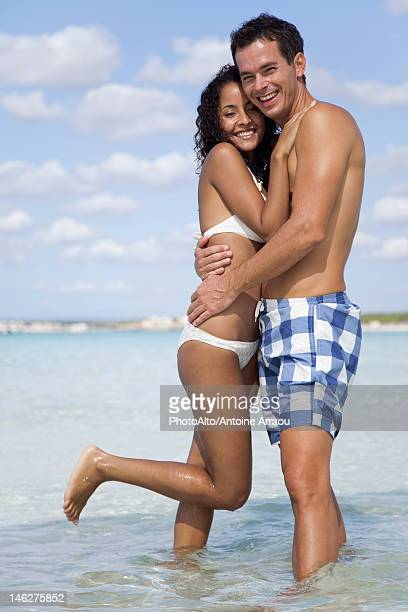 Couple embracing in water at the beach