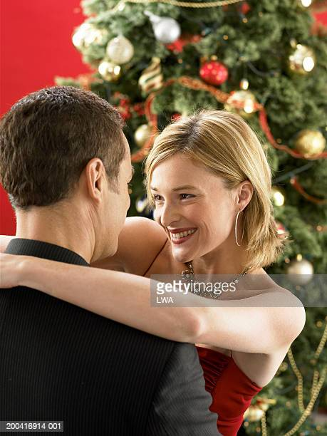 Couple embracing near christmas tree (focus on woman)