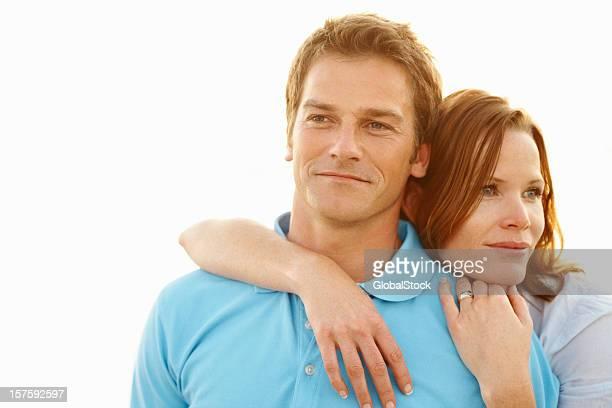 Frau mit Arme um den Mann hinter auf leuchtenden Hintergrund