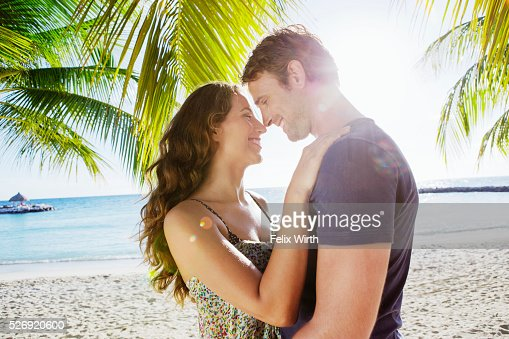 Couple embracing on beach : Bildbanksbilder