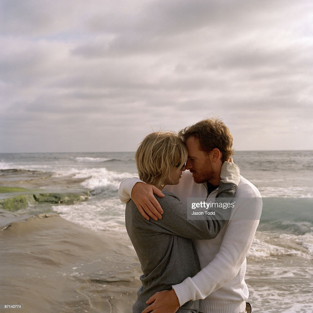 Couple Embracing On Beach Stock Photo