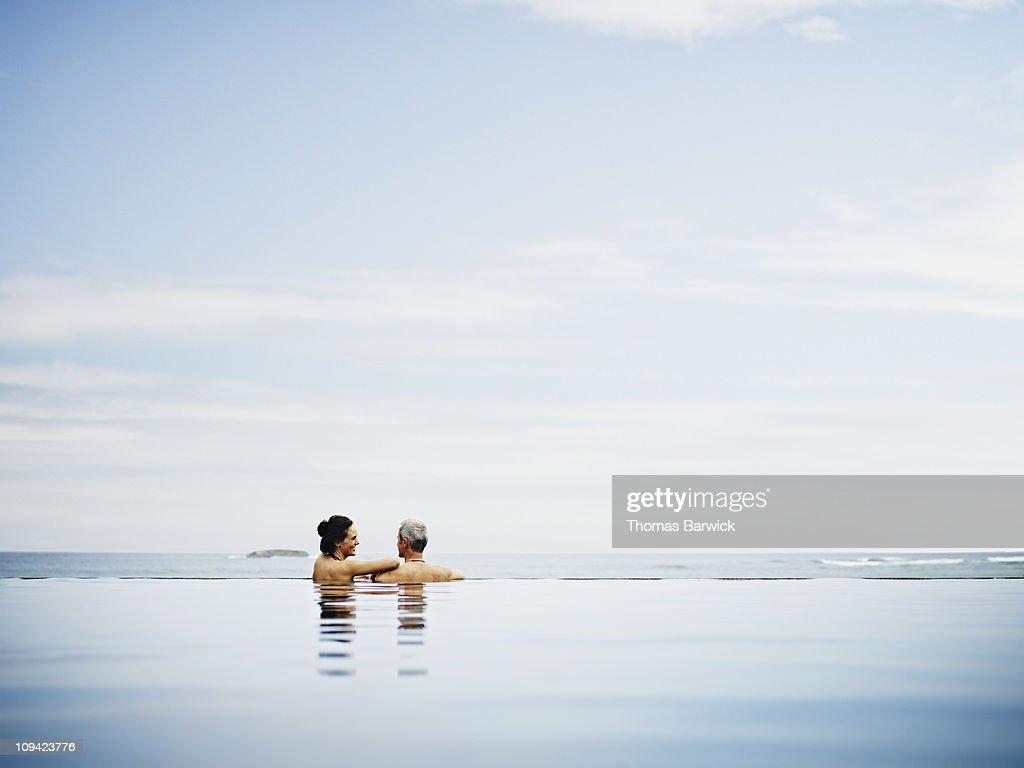 Couple embracing on edge of infinity pool : Stock Photo