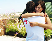 Couple embracing on roof garden, woman holding flower, smiling