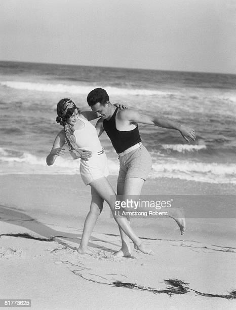 Couple embracing on sandy beach.