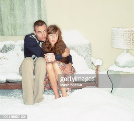 Couple embracing on sofa in snow-filled room